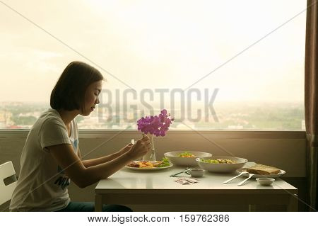 Pensive young woman dinner alone in the room.