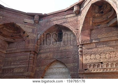 Arcs and carved decorations inside Qutab minar archaeological site in New Delhi, India