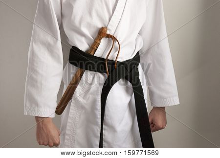 Karate fighter in ready position facing the front with a weapon under his belt.