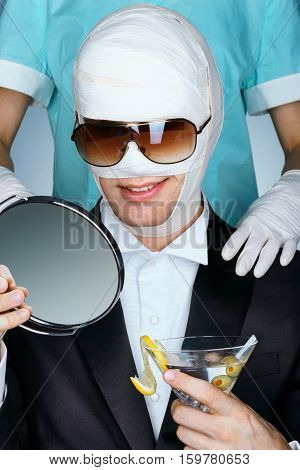 Fashionable man wrapped in medical bandages after facelift together with nurse. Man beauty victim with glass of martini cocktail. Aesthetic Cosmetology concept