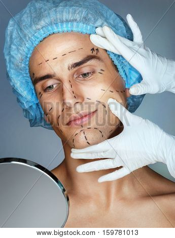 Face lifting. Doctor touches the man's face. Close up of male with correction lines on face for cosmetic surgery. Aesthetic Cosmetology concept