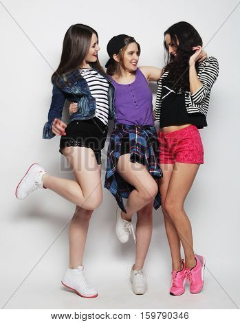 three happy young girls friends dancing of joy in full length, over gray background