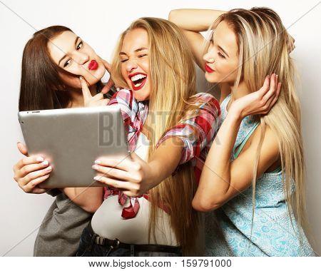 Three girls friends taking selfie with digital tablet, studio shot over gray background