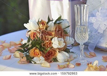Bouquet, champagne glass and presents on table, close-up