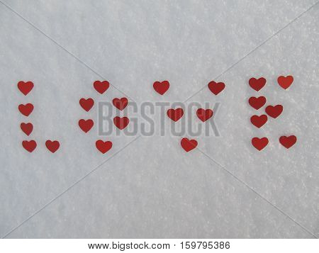 The word love from red hearts in the snow, Valentine
