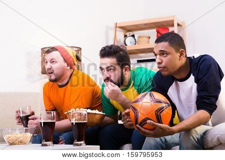 Image of friends waiting for funny or emotional moments while watching football game on TV. Hnadsome men drinking beer and eating pop corn.
