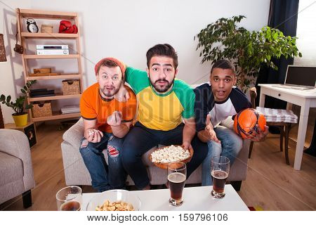 Football concept. Friends are addicted to watching football game on TV. Handsome men drinking beer, eating pop corn and waiting for best moments.