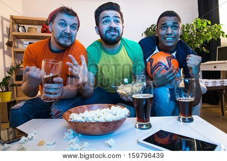Low view of best friends gather together for watching football game on TV. Handsome men drinking alcohol drinks and eating pop corn.
