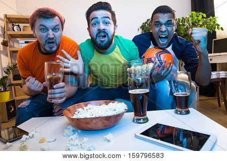 Picture of funny friends watching football game on TV, drinking alcohol drinks and screaming or shouting while catching exciting or amazing moments.