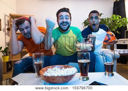 Picture of excited and amazed friends watching football game on TV. Handsome men screaming when someone kicking goal.
