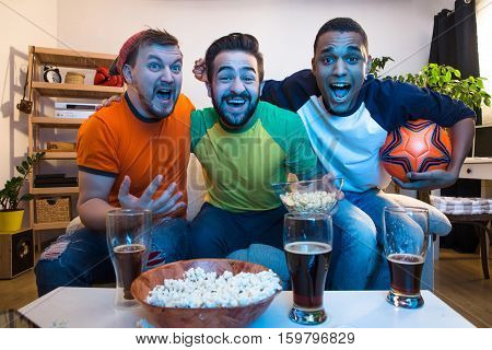 Picture of happy friends watching football game and screaming when someone kicked goal. Football concept.