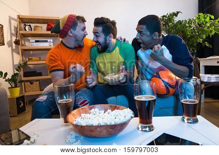 Cheerful old friends having fun watching football game on TV and drinking draft beer at home. Football concept.