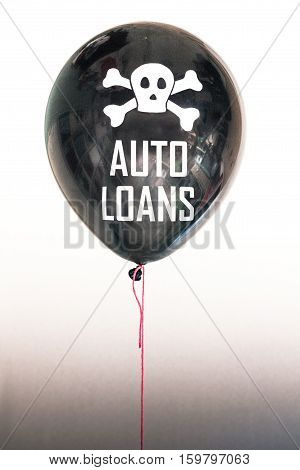 The words auto loans and a skull and cross bones on a balloon illustrating the concept of a student loan debt bubble and its danger to the US national debt and risk for the next GFC.