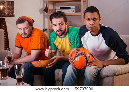 Picture of serious friends watching football game while sitting on sofa or couch and looking at camera. Football concept.