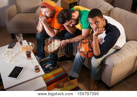 Top view of sad friends watching football game on TV. Handsome man disappointed by game of their best football gamers.