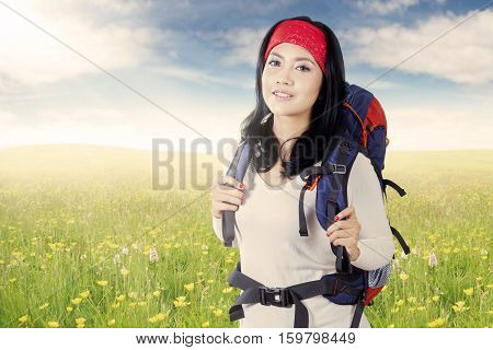 Young Asian backpacker smiling at the camera while carrying rucksack on the meadow