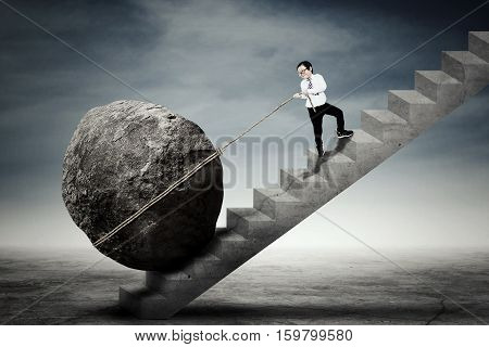 Picture of a little businessman climbing up a stairs while dragging a big stone. Concept of difficulty and persistence