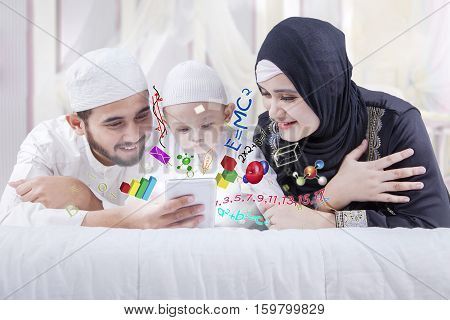 Portrait of cute boy and his parents learning by using a smartphone while lying on the bedroom