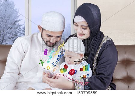 Portrait of cute boy learning math with his muslim parents by using a smartphone winter background on the window