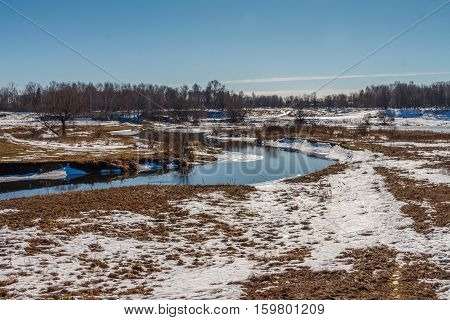 Spring landscape, the river has not flooded, but there is no ice on the banks of the remnants of snow