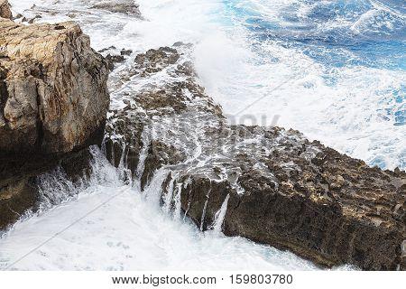White waves breaking over a rocky ledge on the Malta coastline