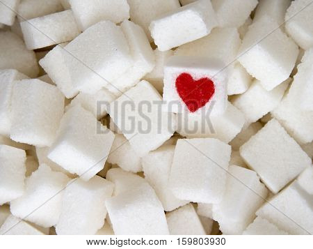 Sugar cubes with a red heart on one of them as background. Top view. Diet unhealty sweet addiction concept