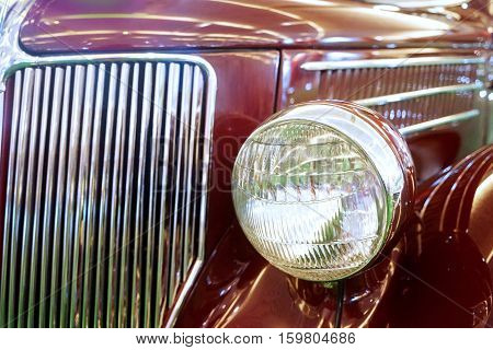 Image of front light of red classic car