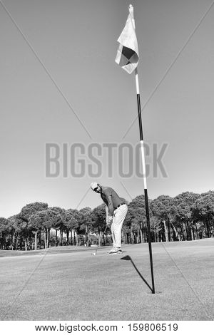 golf player hitting shot with club on course at beautiful morning with sun flare in background black and white
