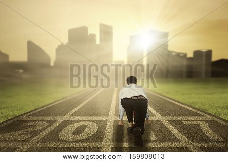 Picture of a young businessman in ready position to run on the track with numbers 2017