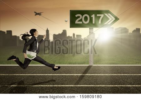 Image of beautiful businesswoman holding paperwork while running on the track with numbers on the signboard