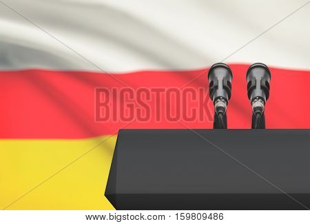 Pulpit And Two Microphones With A National Flag On Background - South Ossetia