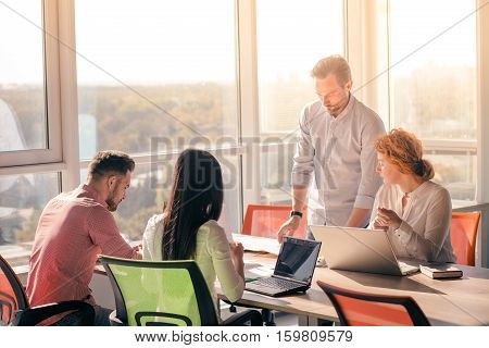 Business people working on laptop computer and listening to their boss in board room in office. Boss explaining one of his worker how to be successful.
