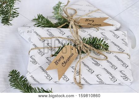 Two beautiful Christmas gifts with tags. Decorated naturally with pine tree twigs and twine over a white background. Extreme shallow depth of field with selective focus on present in foreground.