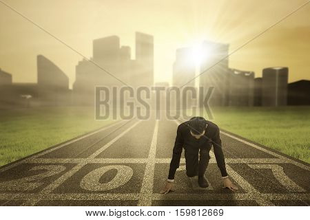 Image of businessman wearing a formal suit in ready position to chase his success with numbers 2017 on the asphalt track