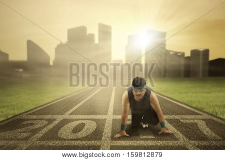 Photo of young obese man kneels on running track with numbers 2017 and ready to run in the field