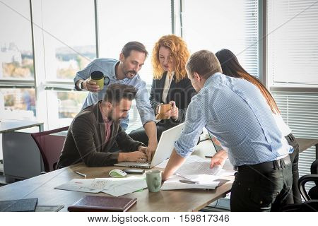 Business people showing team work while working in board room in office interior. People helping one of their colleague to finish new business plan. Businee concept. Team work.