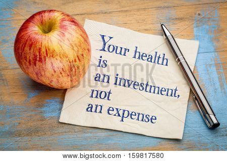 Your health is an investment, not an expense - wellness concept - handwriting on a napkin with a fresh apple