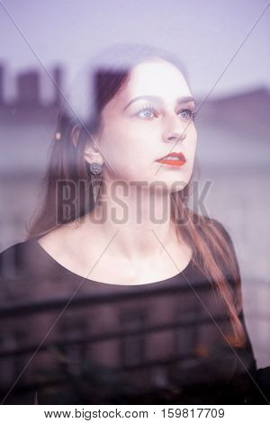 portrait of young brunette woman looking out of the window