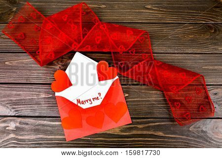 Envelope With Hearts And Red Tape Lying On Wooden Surface
