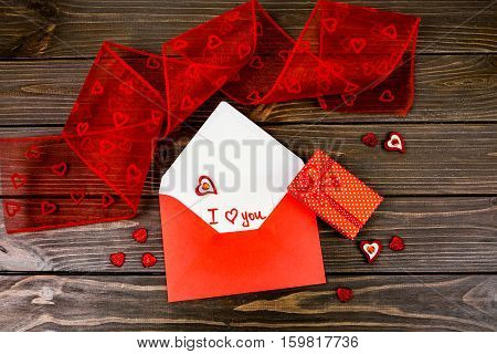 Red Envelope With Card 'i Love You' Inside Lies Among Red Decorative Hearts On Wooden Table