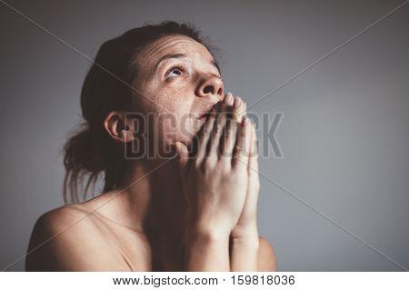 Young woman sad, looking up and praying