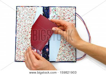 Beautiful handmade scrapbooking holder for travel documents with ribbon closure. Floral fabric design. Femae hands putting passport in. isolated on white background.