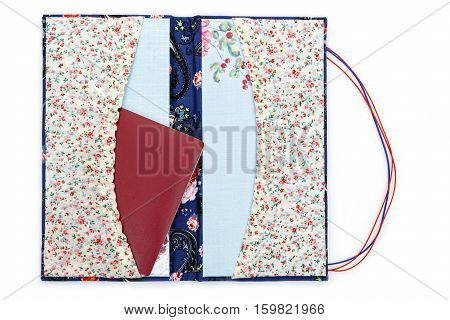 Beautiful handmade scrapbooking holder for travel documents with ribbon closure. Floral fabric design. Passport inside. isolated on white background.
