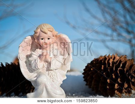 little white angel on a background of blue sky. winter time