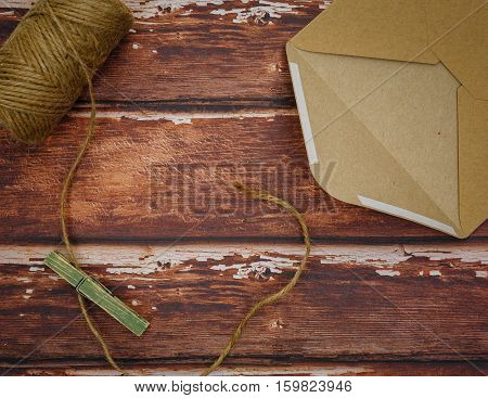 Opened vintage envelope with wooden pin and thread reel lying on rough wood. Copy space.
