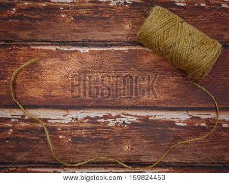 Rough thread reel lying on rough wood background. Copy space.