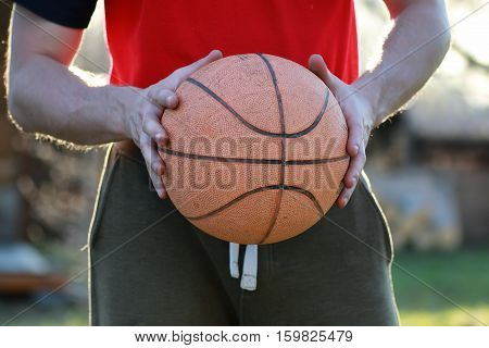 man hand hold basketball ball in sunny evening in summer