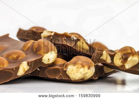 Milk chocolate pieces with whole hazelnuts. Chocolate bar / chocolate background/ nut chocolate / chocolate tower