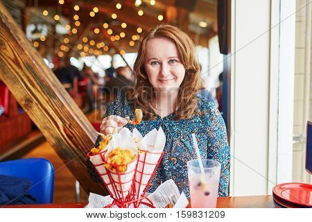 Cheerful Girl Eating Fried Shrimps In Seafood Restaurant
