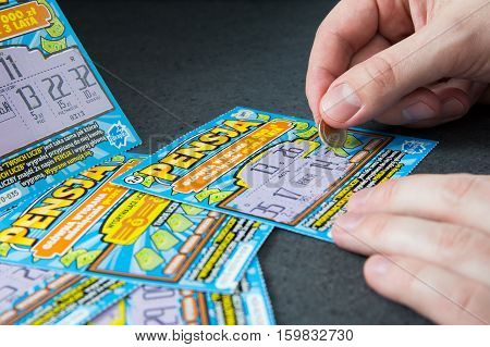 WROCLAW POLAND - NOVEMBER 30th 2016: Man scratches Polish lottery scratchcard. Scratchcard is a small card where areas contain concealed information which can be revealed by scratching off an opaque covering.